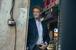 Boyd Holbrook in character, wearing a blue suit and shirt, standing in a doorway