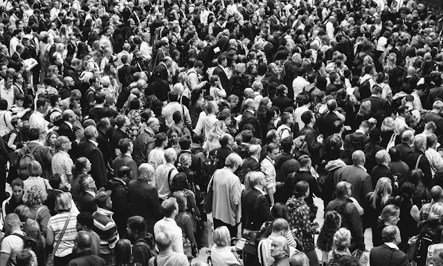 A large crowd of people moving here and there in hurry symbolizing the confusion in life.