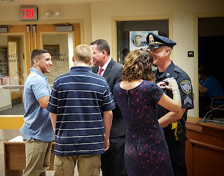 Detective MacLain and Sargent Zimmerman getting their new badges pinned by family members