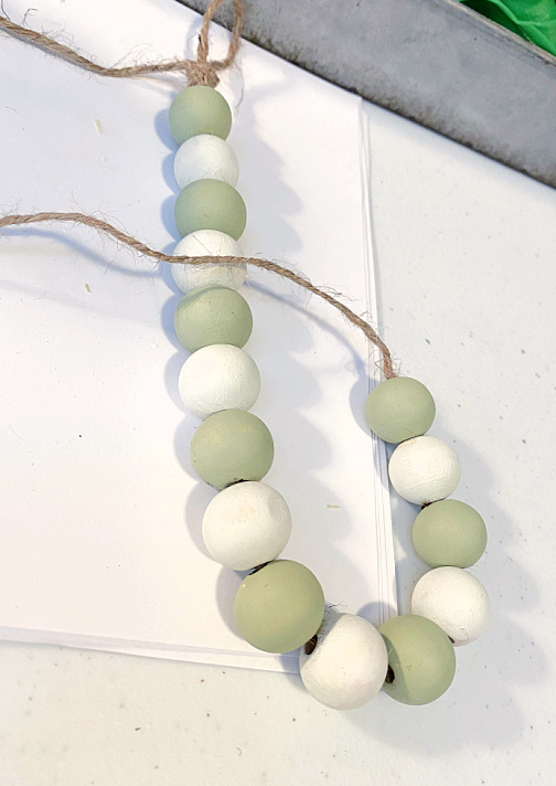 green and white painted beads on jute