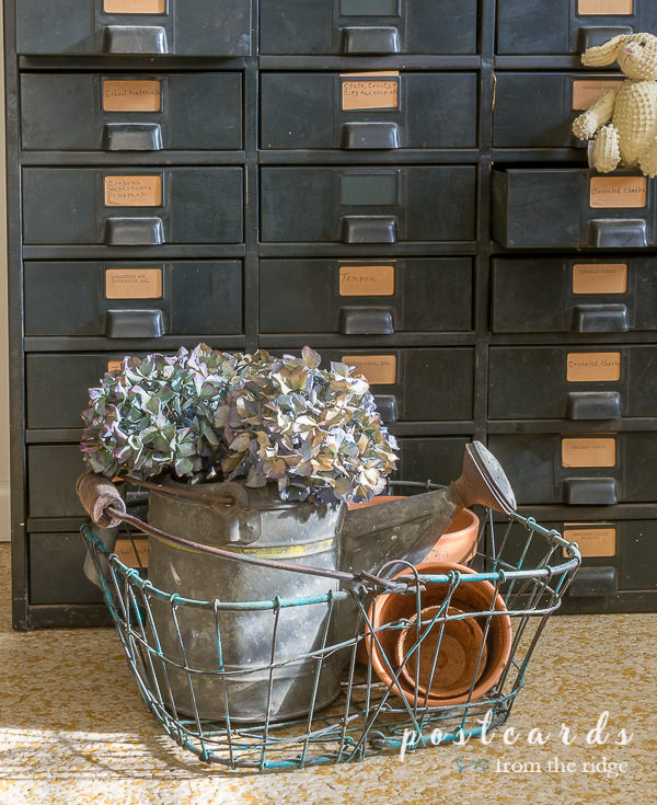 vintage wire basket with dried hydrangeas and terra cotta pots