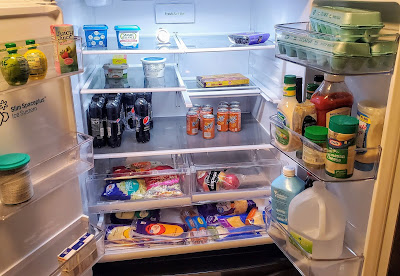 refrigerator with fresh vegetables, salad, eggs, butter, condiments, and an excess of cheese