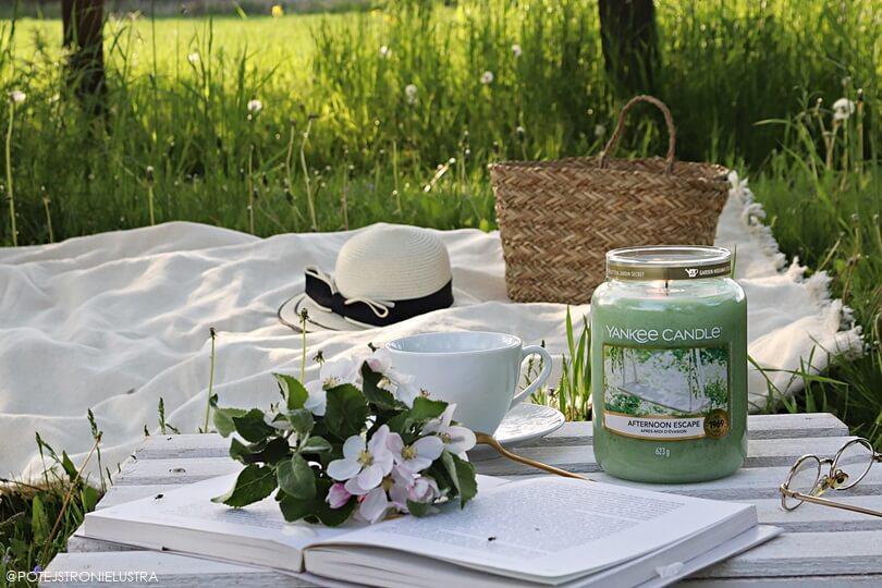 relaks w ogrodzie ze świecą yankee candle afternoon escape, kawą, książką i kocem na trawie