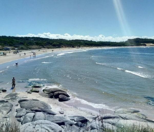praia de aguas calmas e pedras com diversos banhistas na areia