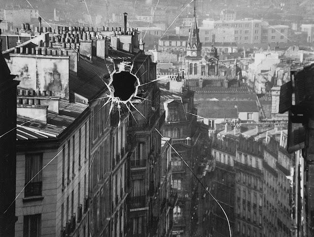 an André Kertész photograph 1929, a bullet hole in a window overlooking a city