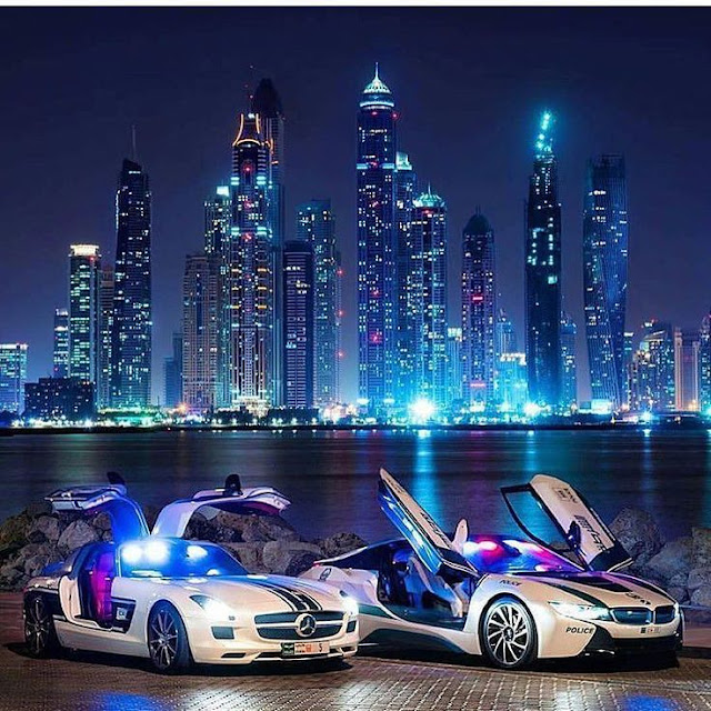 Two expensive cars on the shores of Dubai at night
