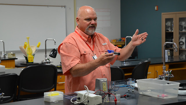 man standing in science classroom and holding an instrument