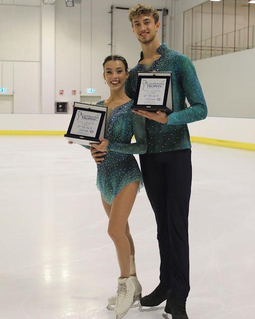Laura Barquero e Marco Zandron posam com placas de segundo lugar do LombardiaTrophy. Eles sorriem para a câmera e vestem trajes azul piscina com brilhos