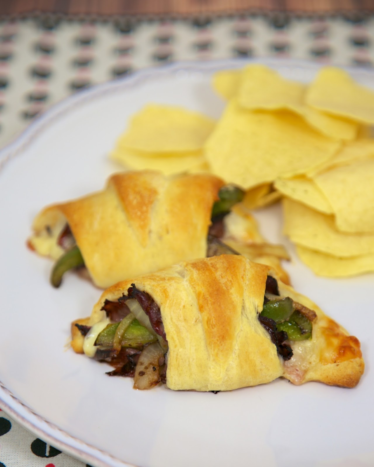Philly Cheesesteak Crescents Recipe - deli roast beef, provolone, horseradish, onions and peppers wrapped in crescent rolls and baked - hot and ready in 15 minutes. A fun and quick lunch or dinner sandwich.