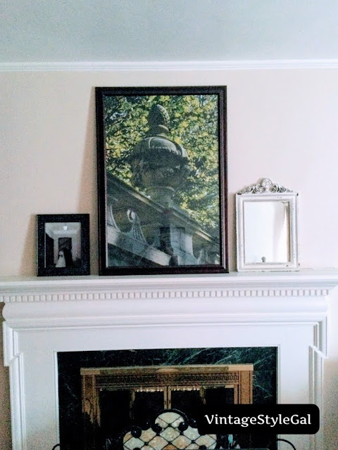 Sparsely decorated mantel with mirror and pictures