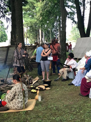 Native American and colonial reenactors talk to visitors at Bushy Run