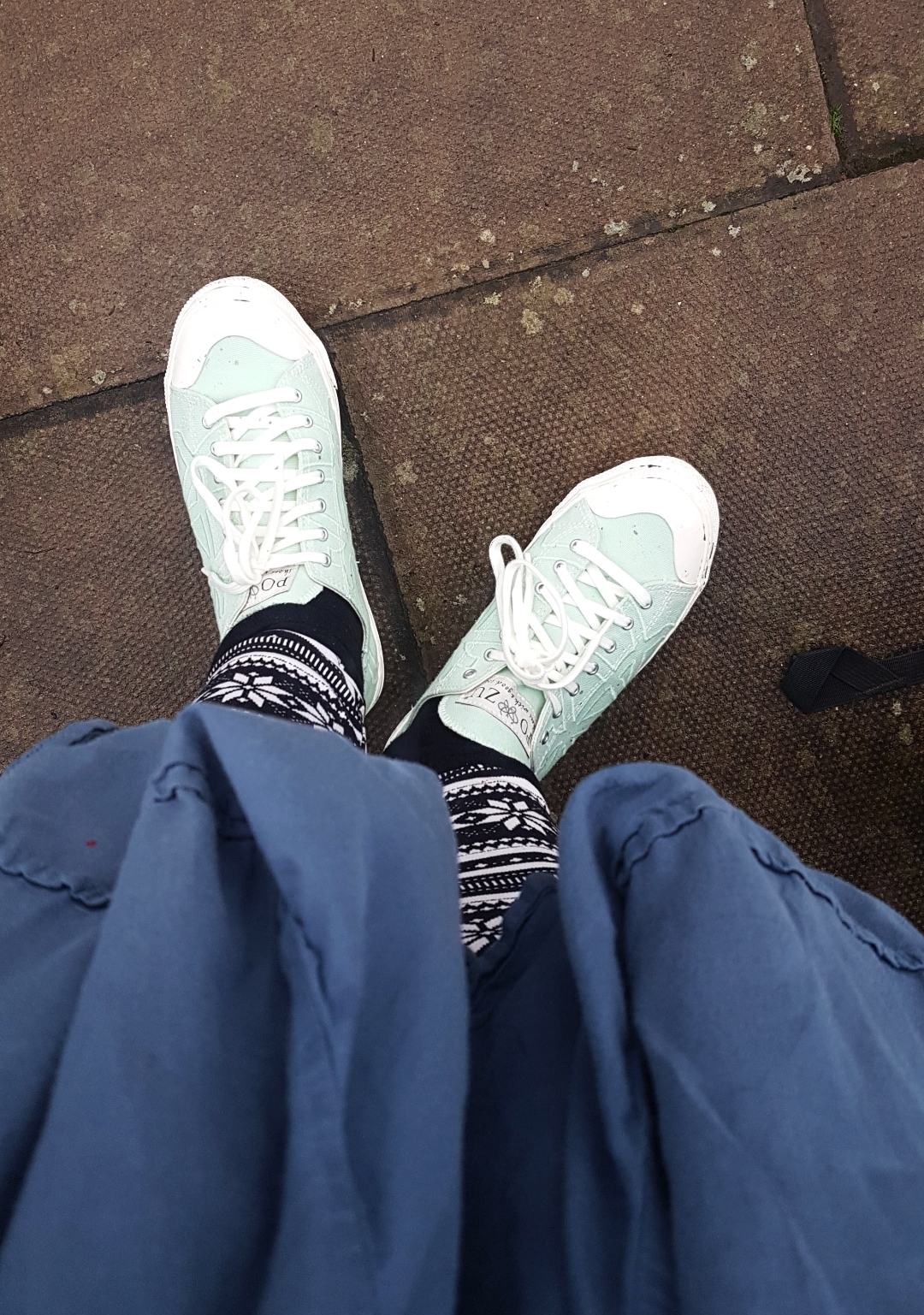 mint green shoes with white laces and the bottom of a flowy blue dress