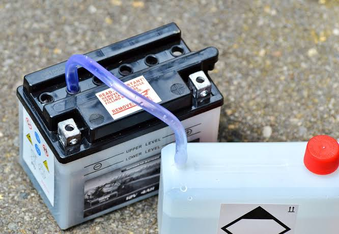 An automobile battery being refilling with electrolyte