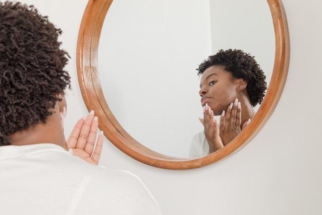 Mulher linda negra unhas grandes se olhando no espelho e passando as mãos no rosto