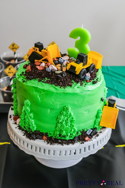construction themed birthday cake with rocks, mini CAT trucks, and dirt