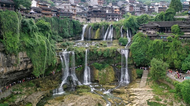 Lost in the middle of a thousand-year-old fanciful ancient town, crouched on waterfall in China