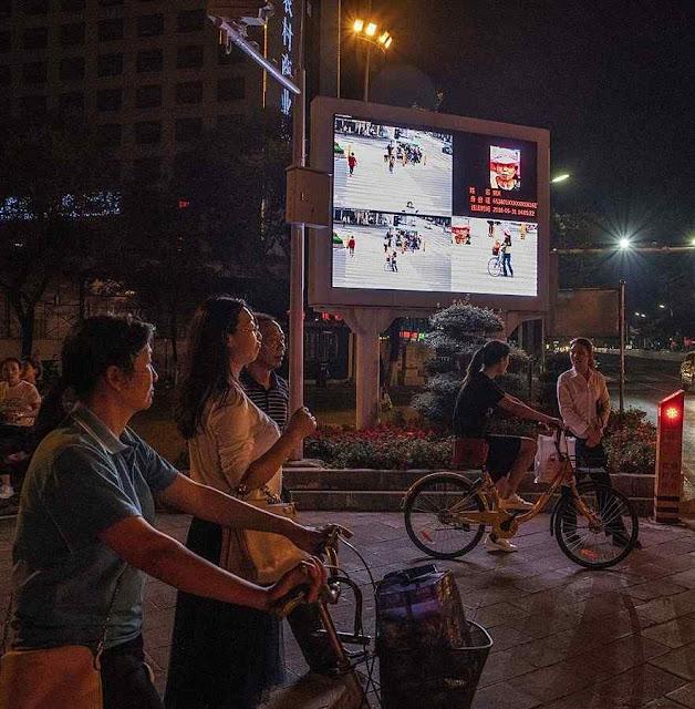 Telão exibe cidadãos de conduta indesejável em Xiangyang, com nomes e RG.