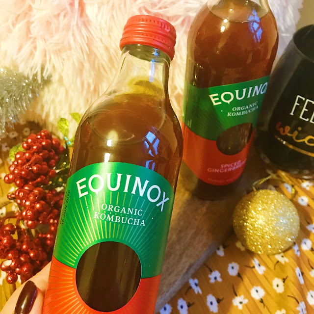 Bottles of Equinox Kombucha on chopping board with baubles and holly
