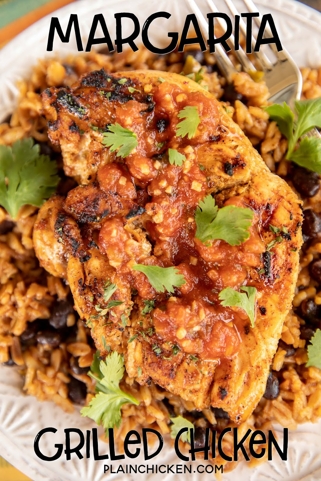 grilled chicken over beans and rice with salsa on a plate