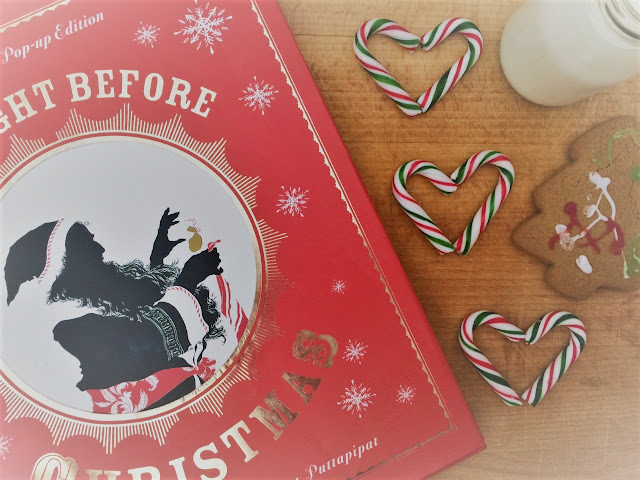 The Night Before Christmas book laid out with candy canes, a Christmas tree biscuit and milk