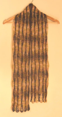 The Woodland Scarf is draped over a wooden coathanger as if it were being worn over the shoulders like a stole. Lengthwise undulating waves of alternating colours can be seen clearly. Each 'wave stripe' ends in a curved scallop shape at the widest point and a thin stitch at the narrowest point.