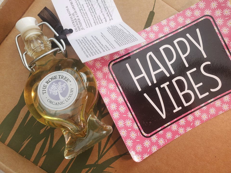 heart shaped glass bottle containing bath oil from The Rose Tree with a pink and black card saying happy vibes next to it