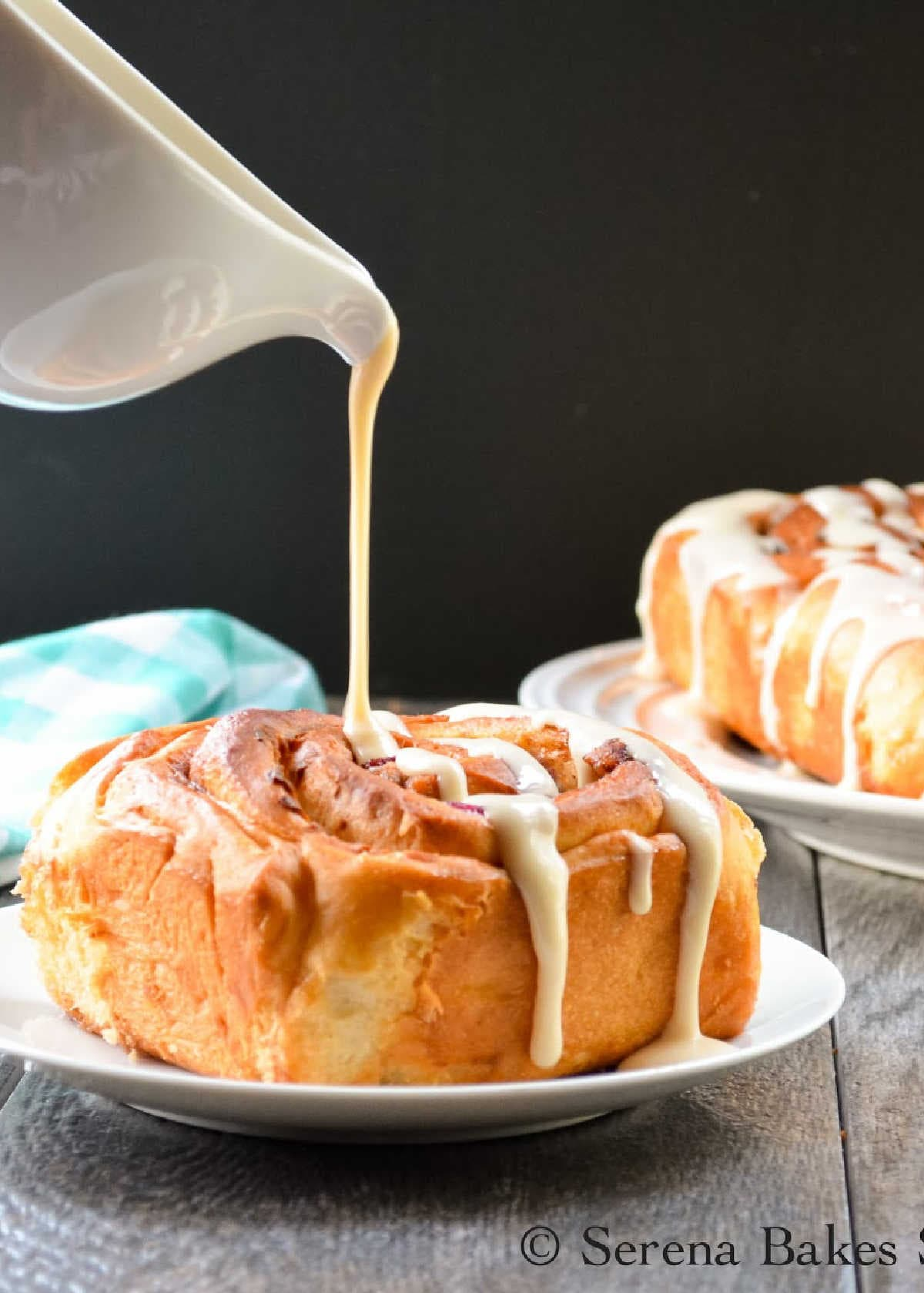 Blueberry Bacon Cinnamon Rolls on a white plate being drizzled with Maple Cream Cheese Frosting.