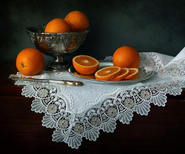 Металлическая посуда и цитрусовые на белом.