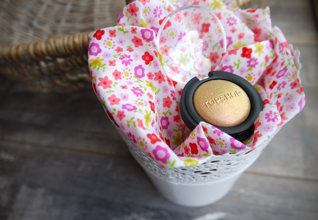 a round black pan of gold/pink glitter sat on a pink floral fabric in a white bucket