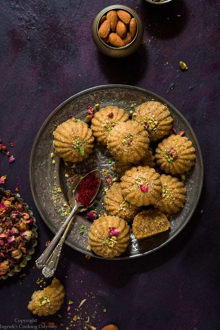 Head shot of microwave churma ladoo placed in a vintage metal plate topped with rose petals and nuts slivers