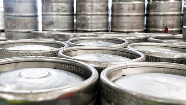 rows and stacks of silver beer kegs