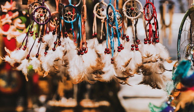 Charms and miniature dream catchers on display at an outdoor selling booth.