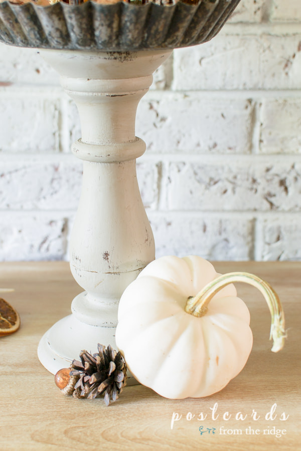 little white pumpkin and pine cone with diy pedestal stand made with wooden candleholders and tart pans