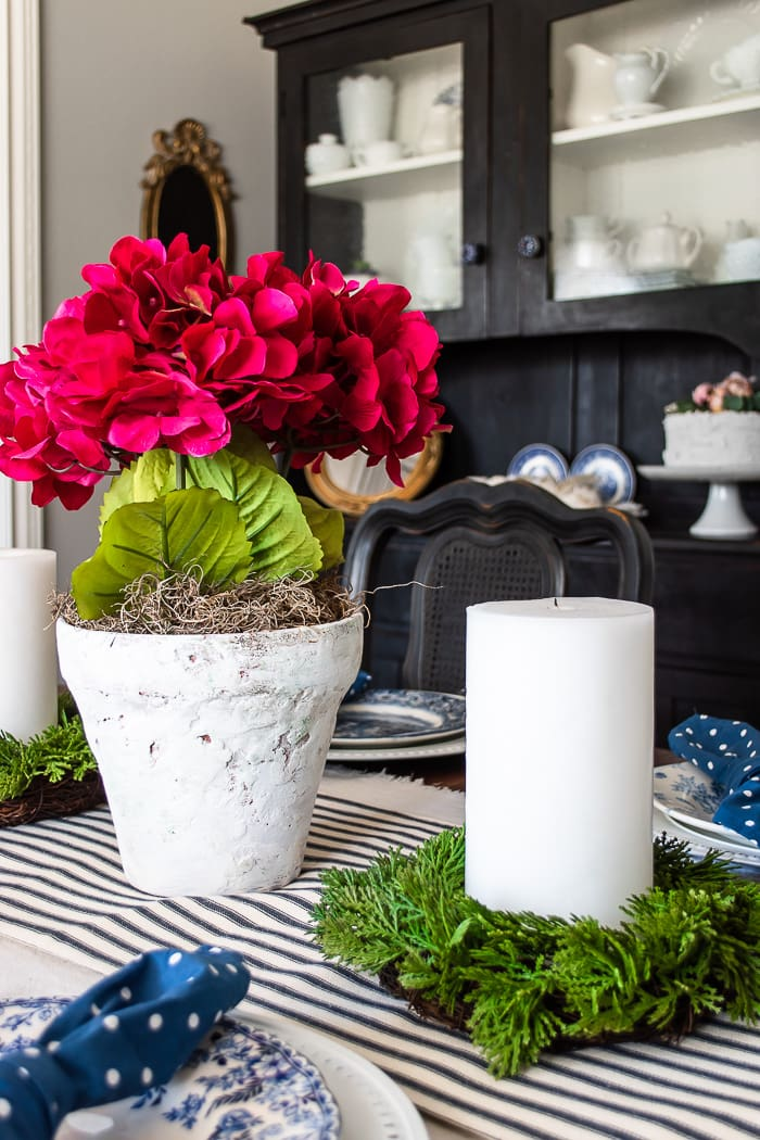 pink centerpiece on blue and white table