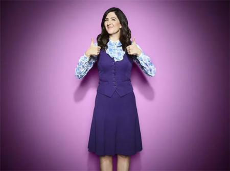 image of D'Arcy Carden, a tall, thin, white woman with long brown hair, dressed in her costume as Janet from 'The Good Place' giving two thumbs-up