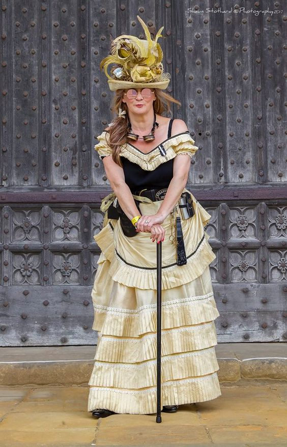 steampunk woman wearing a yellow hat with feathers, yellow dress with pleats, goggles and sunglasses
