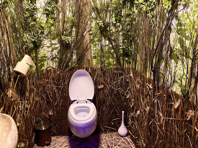 A toilet with forest wallpaper and fake grass stuck to the walls