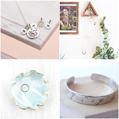 1: a round silver disc on a necklace with dandelions stamped into it. Smaller dics surround it with individual dandelions seeds on them. 2: a wooden triangle on a wall with necklaces hanging from it. 3: a shiny mint green dish with rippled gold edges. 4: a silver cuff stamped with dandelions