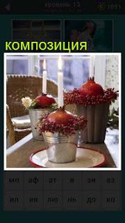 на столе собрана композиция из цветом со свечами и ведра