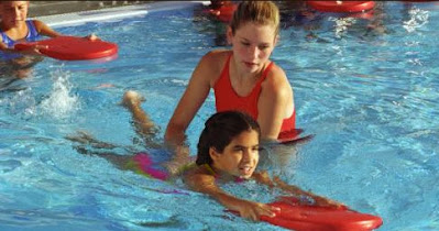 Image of a swim teacher teaching swimming. Maybe she uses these free swimming lesson plans on offer