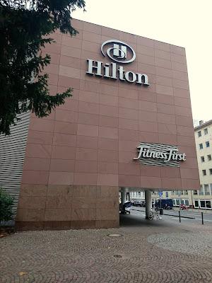 Seitenfassade des Hiltons. Ein großer Block Wand mit Hilton und Fitness First Logo.