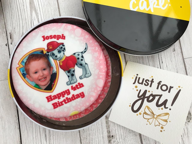 The card and the open tin showing the iced cake
