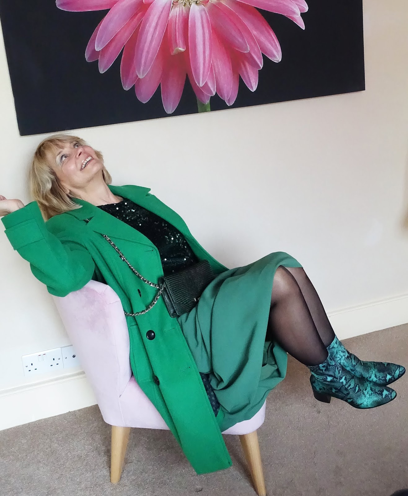 Fun seated shot of over-50s blogger Gail Hanlon in all-green outfit featuring neoprene snakeskin boots