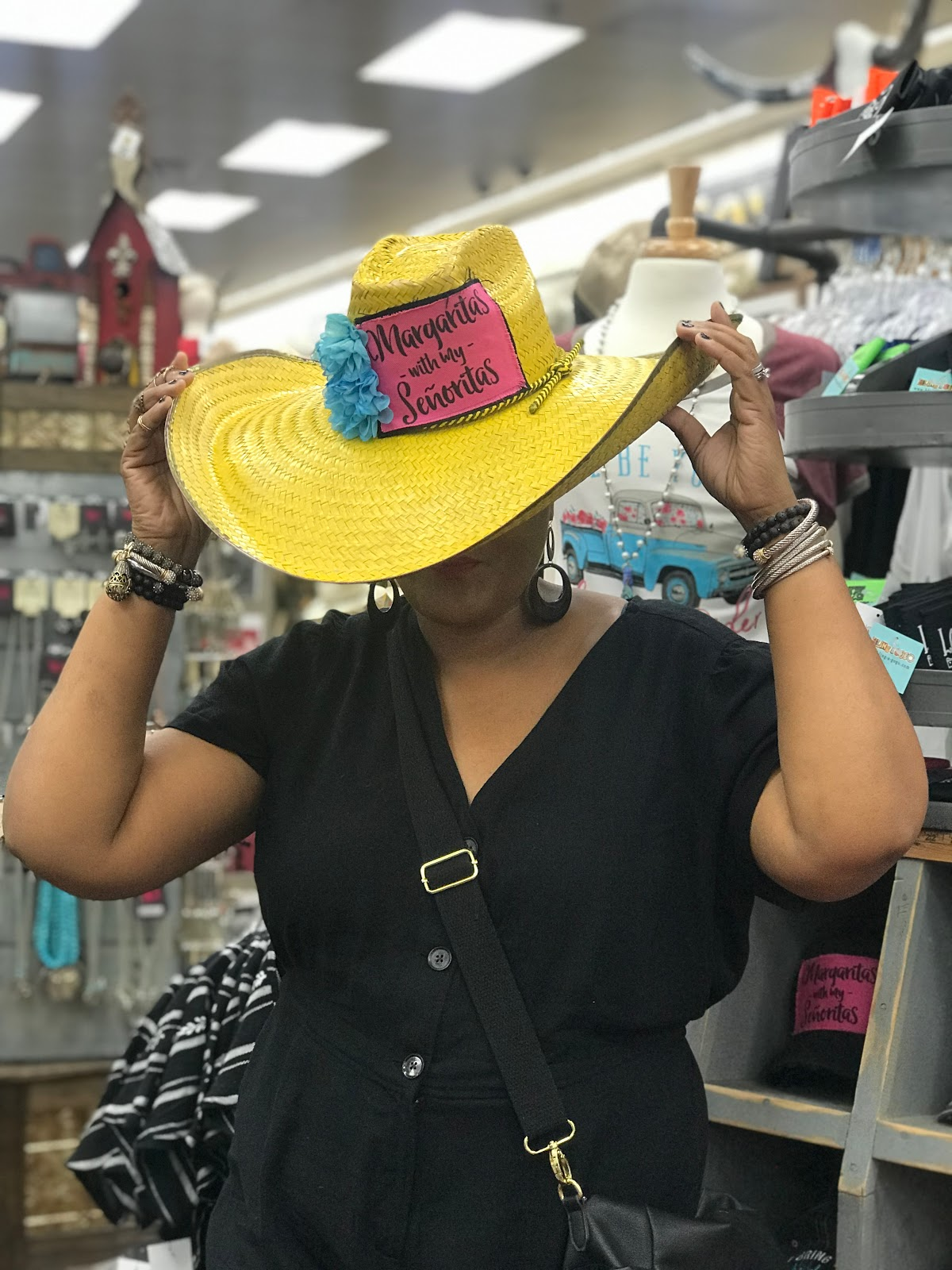 Image: Woman ( Tangie Bell trying on clothes and hats at Bucee Beaver Gas Station in Denton Texas