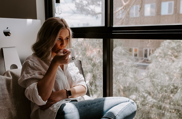 woman by the window looking out drinking coffee