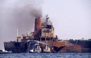 Firefighters attend the Agip Abruzzo, with the enormous gash in its side caused by the collision clearly visible