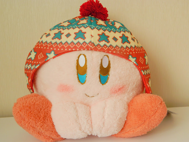 A photo of a big kirby plushie. He is a round, pink character from nintendo games.