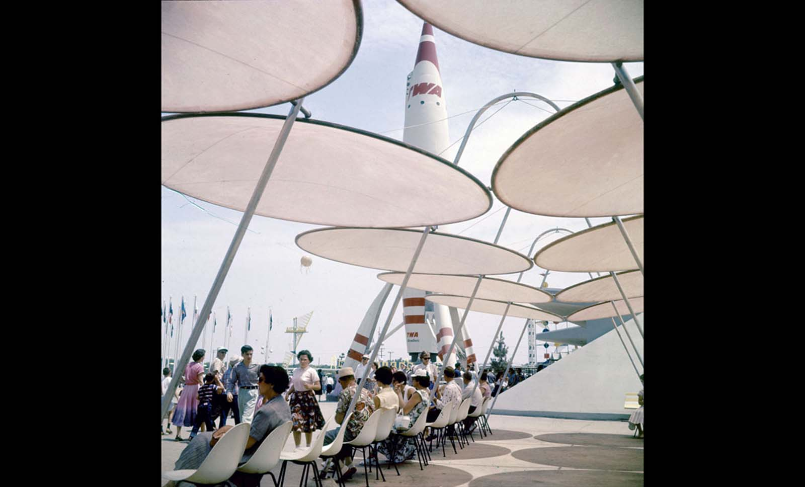 Park attendees relax under sunshades near a TWA rocket in Disneyland in July 1955.