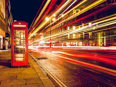 colorful time lapse image of lights passing a London phone booth