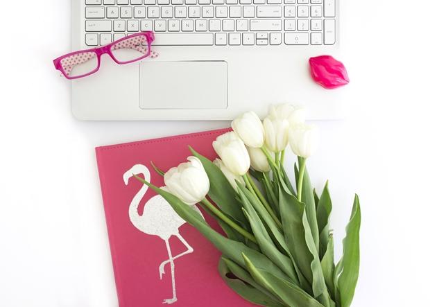 Imagem home office notebook prata com uma agenda na rosa na frente com flamingo na capa